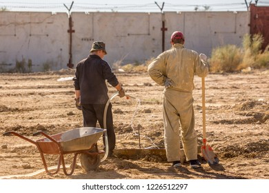 Two tradesmen with a trolley, a construction worker in special clothes spread out a mixture of cement