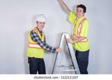 Two tradesmen using a ladder.