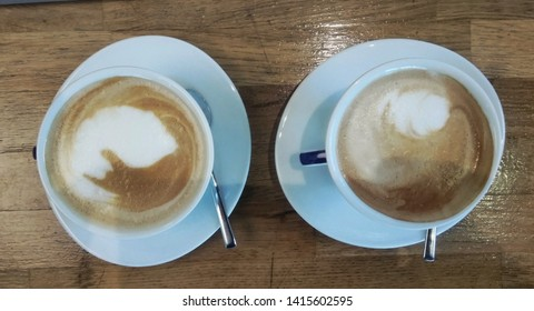 Two traditional capuccino coffies over a recycled wood table. Flat Lay display of two cups of coffee