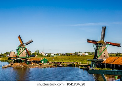 Two traditional dutch windmills located by the river in Zaanse Schans, Netherlands.