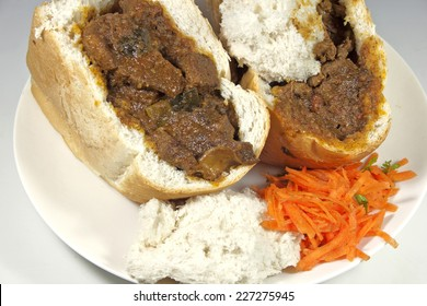 two traditional south african bunny chows with carrot and coriander sambal