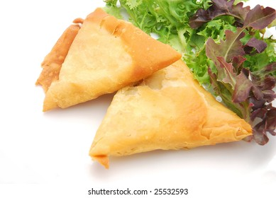 Two traditional South African Samosa pockets filled with chicken and beef mince with lettuce on plate isolated on white studio background