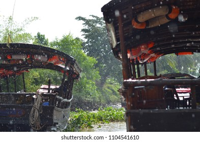 Two traditional wooden boats on a river in the Mekong Delta, Vietnam. Heavy rain is falling. Lush jungle surrounds the boats.