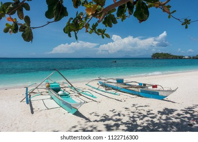 Two traditional wooden fishing boats docked on a pristine white-sand beach in north Cebu, Philippines - Shutterstock ID 1122716300