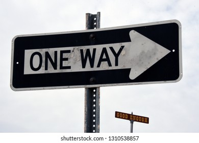 """Two traffic signs, one saying """"One Way"""", the other one """"Good enough"""""""