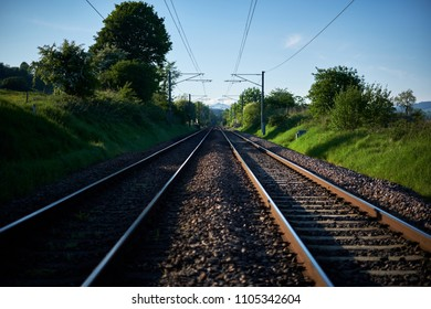 Two train tracks merge in the distance on a clear, sunny day on an electrified line