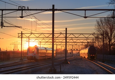 Two trains leaving a railway station during a winter sunrise.