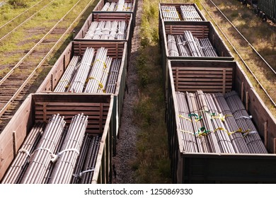 two trains on the railroad cars which steel billets for pipes, cars on railway tracks
