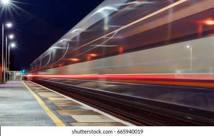 Two trains passing through a UK station at high speed in opposite directions captured as motion blur