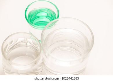 two translarent glasses and one green glass with water