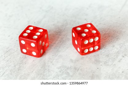 Two translucent red craps dices on white board showing Yo (Yo-leven) (number 6 and 5)