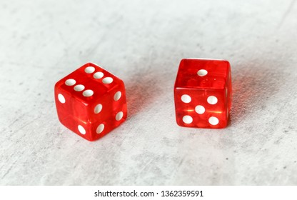 Two translucent red craps dices on white board showing Natural or Seven Out (number 6 and 1)