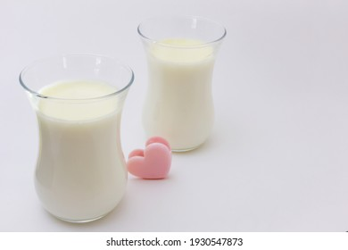 Two transparent glasses with white creamy Italian dessert Panna Cotta on a light background.