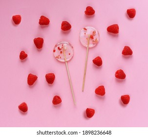 Two transparent lollipops on a pink background. Nice photo. Raspberry berries