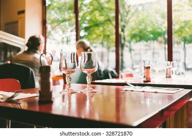 Two transparent wine glasses standing on the table in modern restaurant
