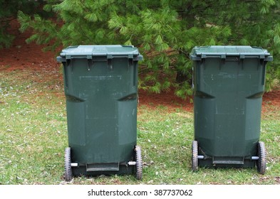 Two trash bins on wheels are on the green grass against a backdrop of trees waiting for a neighborhood garbage truck to collect the waste.