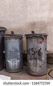 two trash cans of galvanized sheet steel standing next concrete plaster wall in a backyard