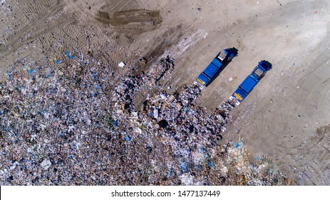 two trash trucks dump waste products polluting our environment in an open landfill