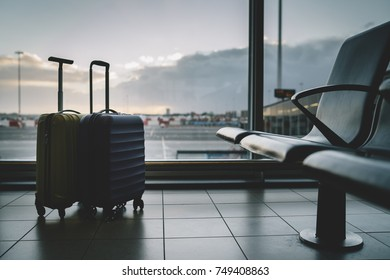 Two travel suitcases in airport terminal waiting area, beautiful sunset on the background, holidays concept
