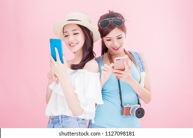 two travel woman smile happily and use phone on the pink bakcground