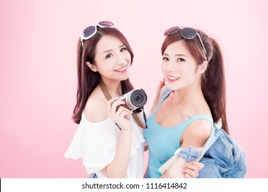 two travel woman take camera and smile happily on the pink background