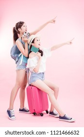 two travel woman take camera and passport smile happily on the pink background