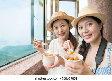 two traveler girls love the famous Taiwan local food on top of Jiufen hill of Taipei city.
