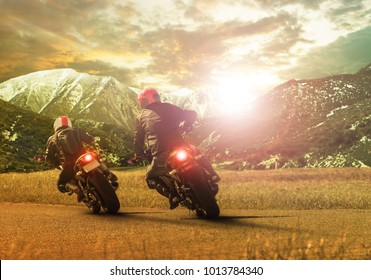 two traveling motorcycle leaning on sharp curve