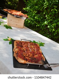 Two trays of Italian pizza, on a table in a garden