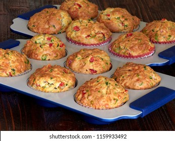 Two trays of savory muffins with cheddar, spinach and red peppers