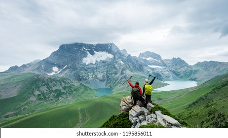 Two trekker action take a photo at past Gadsar lake and a meadow at kashmir great lakes trek in kashmir. Two person in the mountains and twin lakes of Kashmir, India.