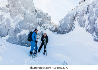 Two trekkers with trekking poles rest under an icy rock in the mountains in the winter.