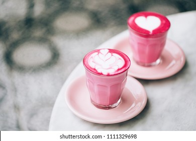 Two trendy beetroot lattes with latte art and flower petals on the foam.