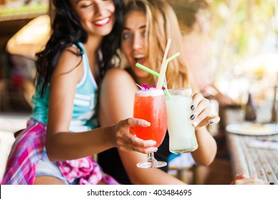 Two trendy cool hipster girls, friends, the blonde and the brunette drink cocktails at the cafe on the beach. Dressed in colorful shirts and shorts.