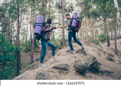 Two trendy people, spouses on vacation, expedition, holding hands, wearing casual checkered shirts and jeans, traveling, spending spare time on fresh air in wild wood, climbing, girl and bearded guy