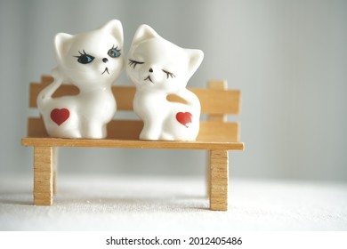 two trinkets cats on a bench