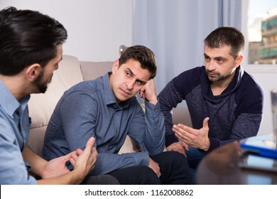 Two troubled men having serious talk with their friend at home