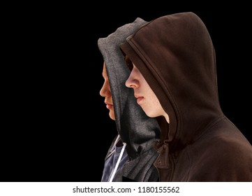 Two troubled teenage boys friends with black hoodie standing next to each other in profile isolated on black background