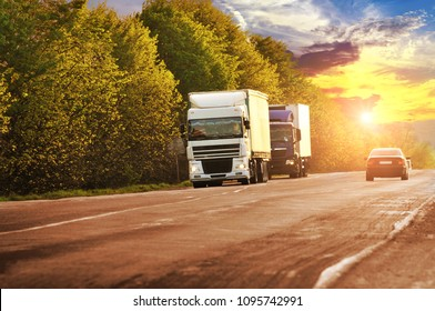 Two trucks with a black car on the coutryside road with green trees against night sky with sunset