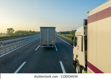 Two trucks driving motorway in early morning