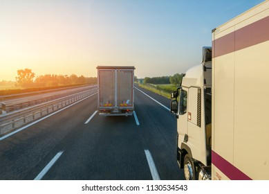 Two trucks driving motorway in early morning, sun flare effect