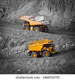 Two trucks in a modern gold mine in Australia. Spot color large haul trucks transport gold ore from the pit, Open cast mine. Spot color water truck, Yellow trucks, black and white background.