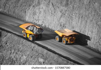Two trucks in a modern gold mine in Australia. Spot color large haul trucks transport gold ore from the pit, Opencast mine. Yellow trucks, black and white background.