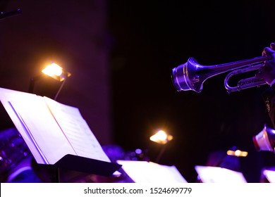 Two trumpet bells with cup mutes playing music from a music stand with attached lighting that gives off a warm glow and adds to the big band jazz concert atmosphere in blue and purple stage lights