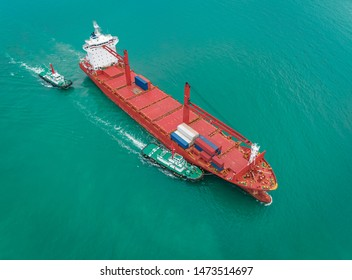 two tug boat drag container ship in shipping port area, thailand.