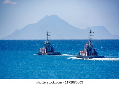 Two Tugboats Cruising Out to Sea Towards Hazy Hills