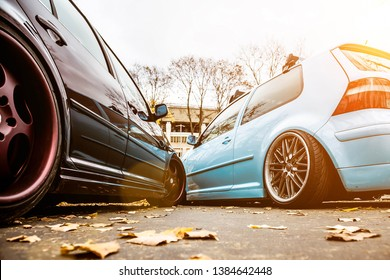 Two tuned cars. Light blue and brown collided, accident on the road. Not a serious accident with lowride custom cars on light allow wheels, redecoration. Bumper damage