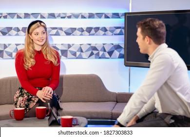 Zwei TV-Gastgeber, die miteinander reden, während sie auf einem Sofa in einem Filmstudio sitzen, sind dabei, eine Fernsehsendung zu filmen.