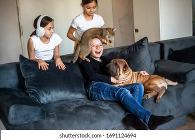 Two tween kid sit in sofa and playing with pet in home room. The girl listen musik on headphones