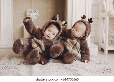 Two twin babies boys. They are setting together in a deer costumes.twin, baby boys wearing deer hats.
